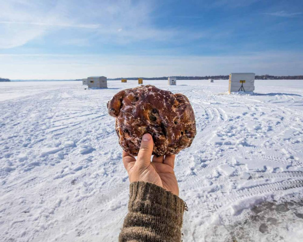 Hand holding giant Hanks Pastries Apple Fritter in Port Perry Ontario