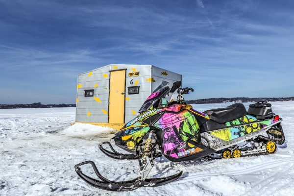 ice fishing hut in Ontario next to a snowmobile