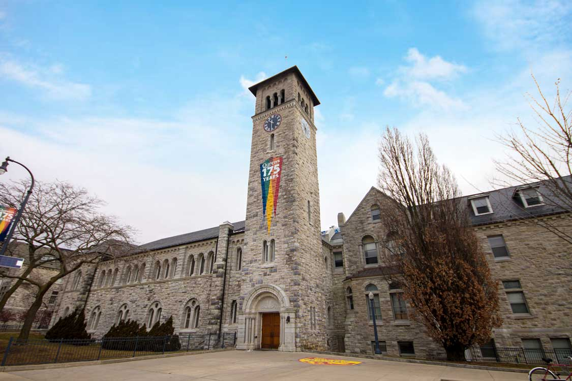 Tower of a university library against a blue sky with a rainbow flag hanging