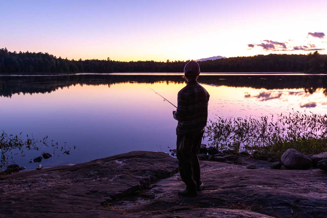 Fisherman casting on the shores of a lake under a pink sunset