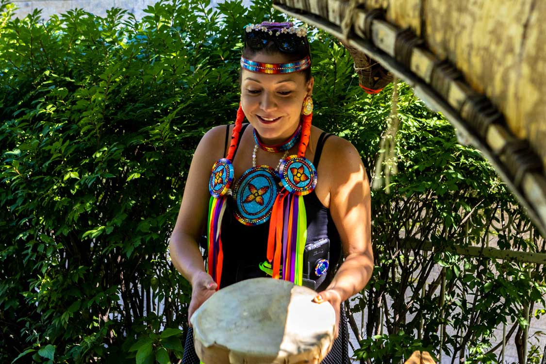 An Indigenous woman in Canada playing a drum and wearing regalia