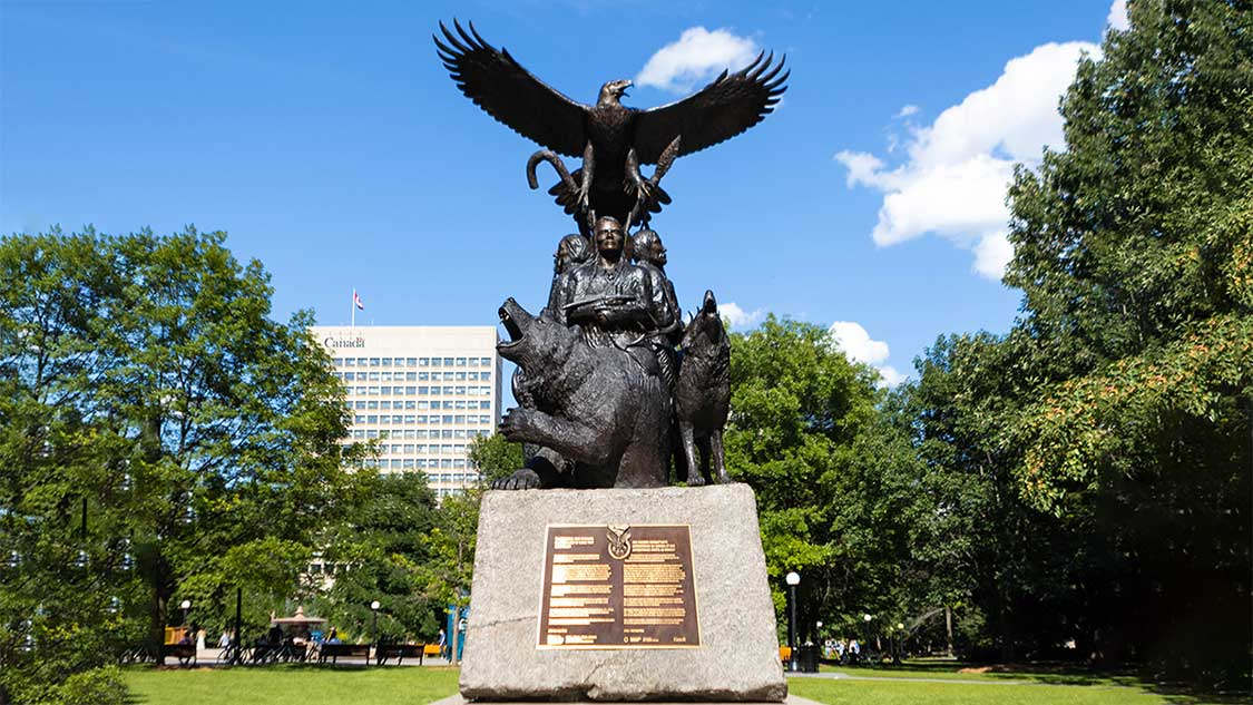 Monument feature Indigenous soldiers surrounded by a wolf and bear and topped by a Golden Eagle