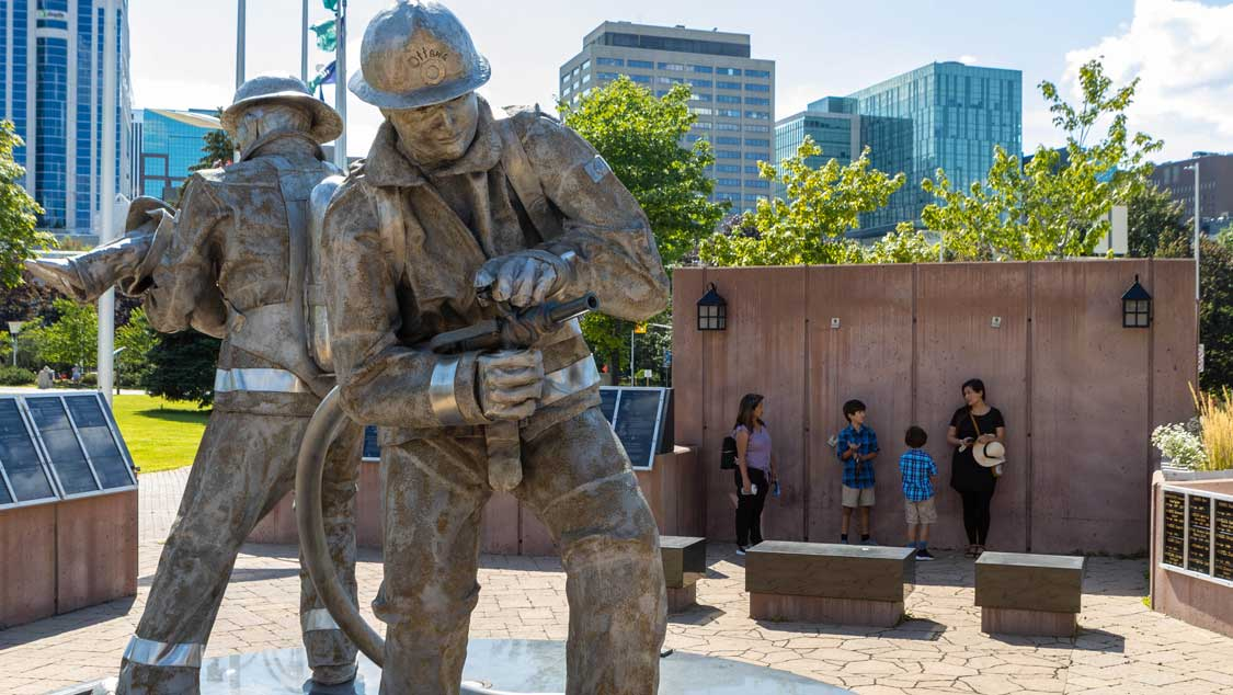 A woman talks to a mother and her children about a monument to firefighters on an Ottawa art tour