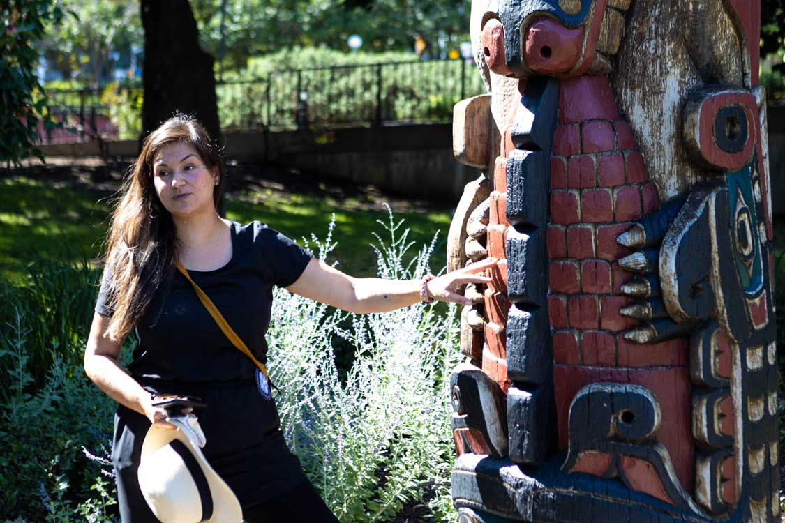 A metis woman holding a hat stands next to a Totem pole in Ottawa's Confederation Park