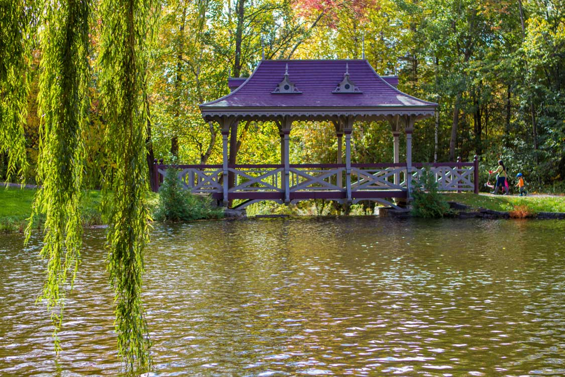 A Japanese-style pagoda bridge on a lake surrounded by weeping willow trees