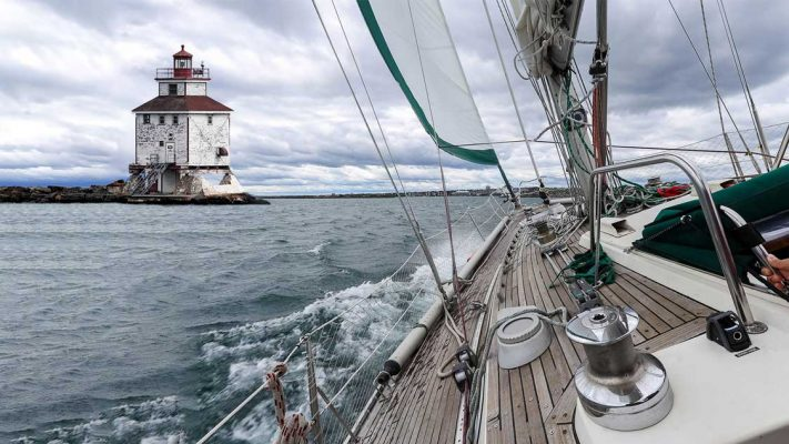 A sailboat sailing towards a lighthhouse on Lake Superior