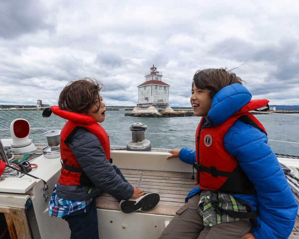 Two boys laugh as they sit on a sailboat boating past a lighthouse in Thunder Bay