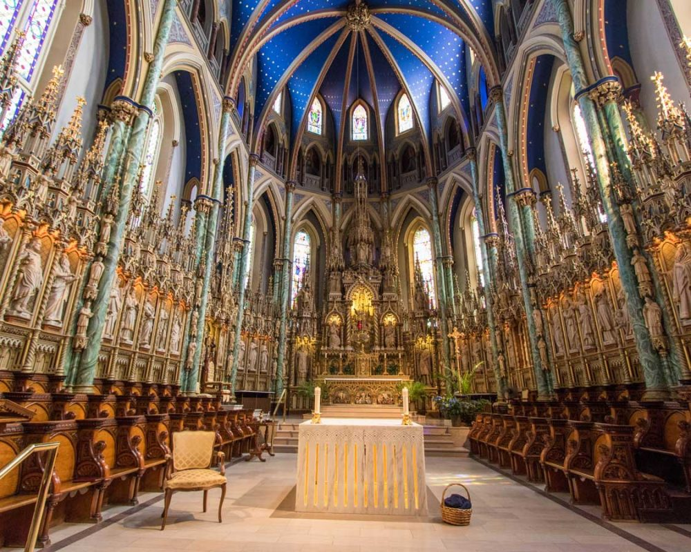 Dramatic interior of an Ottawa cathedral with candles and a bright blue ceiling