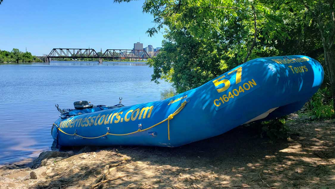 Blue white water raft on a beach with the city of Ottawa in the background