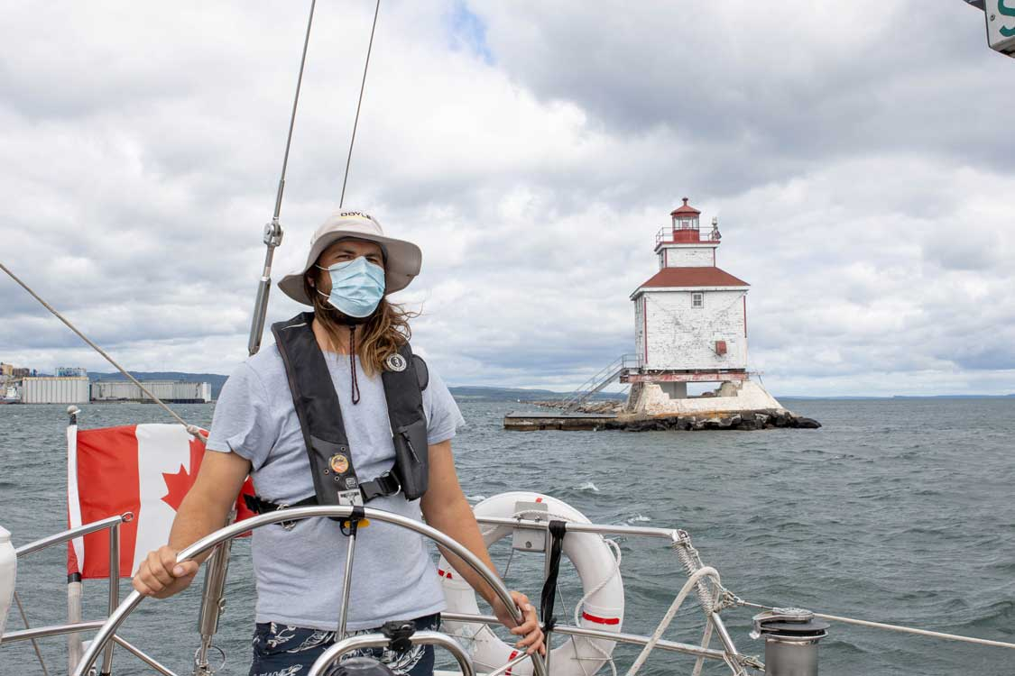 A boat captain passes a lighthouse on a boat with a Canadian flag flowing in the background