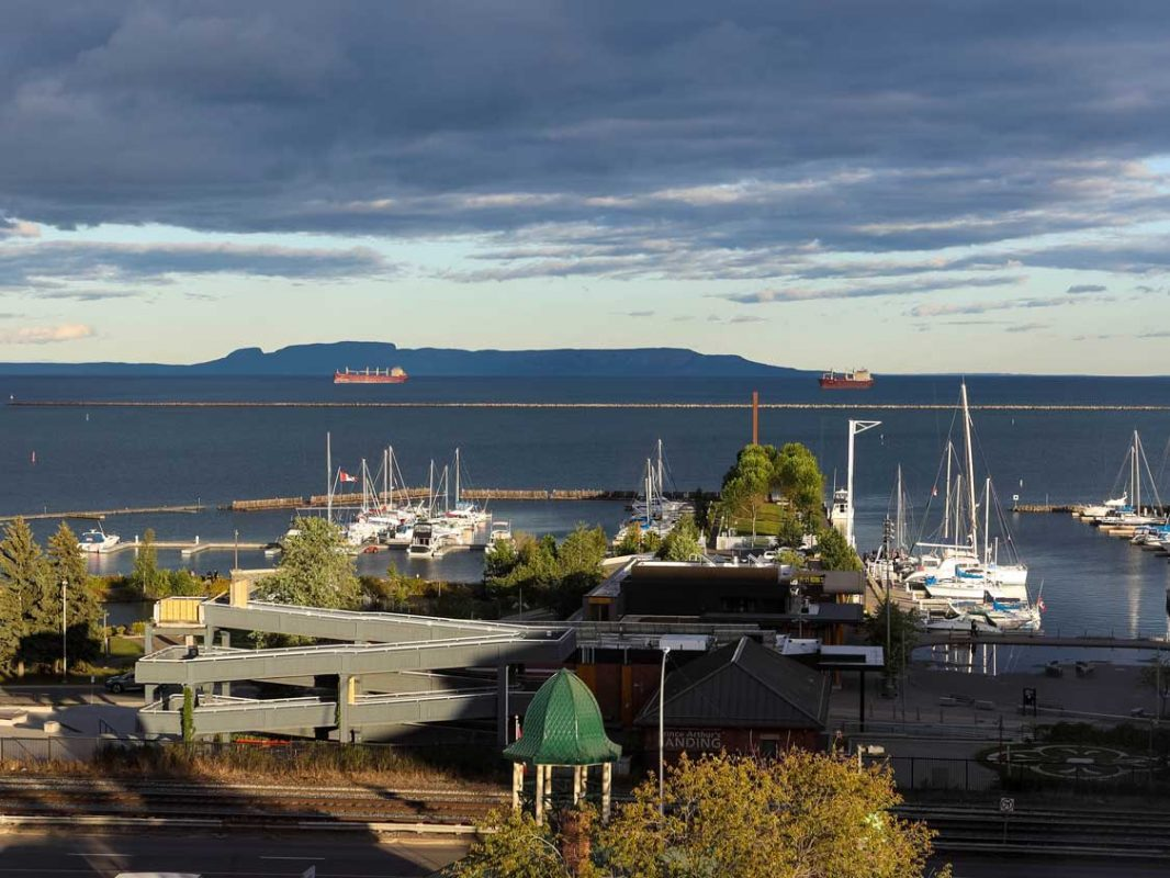 A northern Ontario marina with shipping boats and a large hill shaped like a sleeping giant