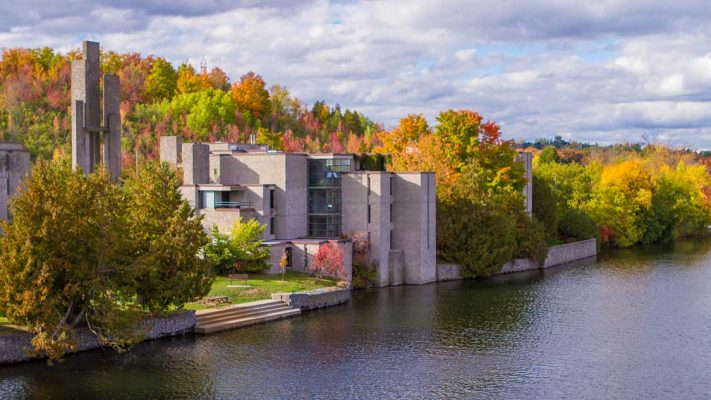modern buildings surrounded by colourful trees beside the Otonabee River in Peterborough, Ontario