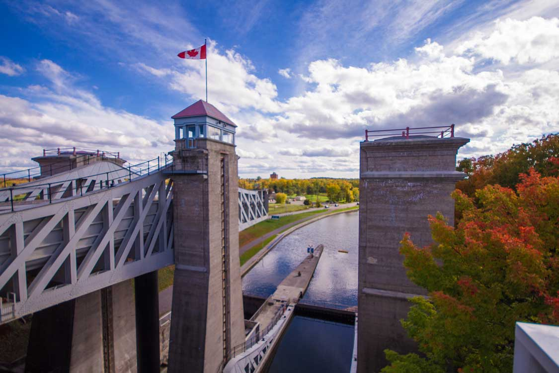 A Canadian flag flies at the top of of a stone lift lock in Peterborough Ontario