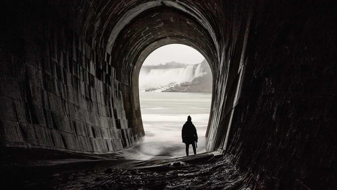 woman standing at spillway of Niagara power plant looking at Niagara Falls