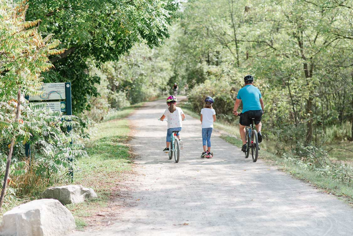 A father bikes with his daughters on the SC Johnson Trail in Brantford, Ontario